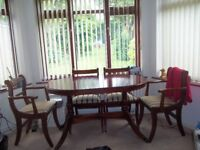 Dining table with 4 chairs plus 2 carvers, chairs have Regency-style striped seats
