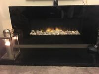 Black wall-mounted electric fire with black granite hearth
