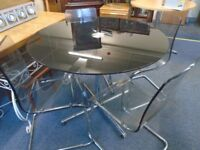 black round glass table with 4 transparent chairs.