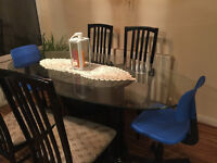 oval glass top dinning table with 6 chairs and black table pedestal