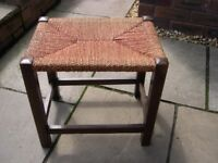 A wood framed stool with red rush seat.