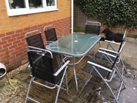 A stylish large garden black tempered glass table and six folding chairs