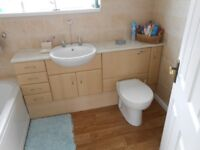 Bathroom units and sink along with toilet