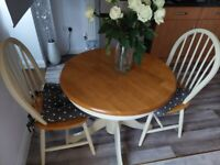 Cream and wood dining table and 2 chairs. Good condition.
