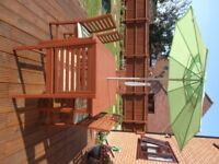 Wooden patio garden table and chair set, with parasol.