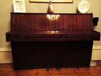 Modern upright piano with a high gloss wood finish in excellent condition.