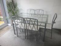 Glass top table and 6 dining chairs, white seats with silver/grey frame