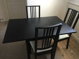 Black table and three chairs .