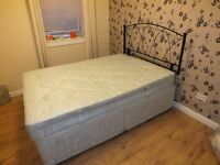 Double divan bed with wrought iron headboard