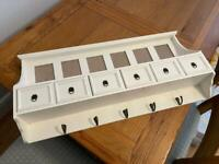 Coat rack with integrated drawers and picture frames