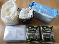 A bundle of incontinence products - pants, pads, protective sheets.