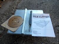 Powered tile cutter with spare blade.