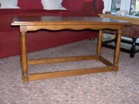 A solid oak coffee table with attractive wave effect skirting.