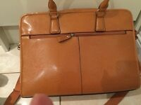 Mans tan brief case has all different parts for keeping things new