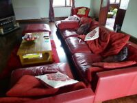Pre-owned red leather suite comprising large settee, two large seats & pouffe in very good condition