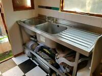 Commercial catering double sink unit complete with mixer taps for both sinks .