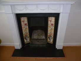 Cast iron fireplace with tiled inset with white wooden surround
