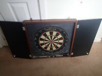 Dart board in cabinet and sets of darts