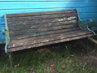 Wooden garden bench with iron arms and feet