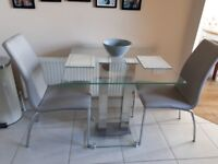 Square glass table and two faux leather grey chairs.