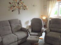 beige suite comprising 2seater setee,reclining chairand reclining swivel chair with footstool