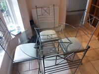 Glass topped dining table with 4 chairs. Good quality metal frames.