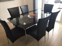 Glass dining table and 6 black faux leather chairs, chrome legs.