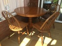 Round wooden dining table with 4 matching chairs