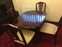 Mahogany Dining room table with four cream covered high back chairs