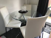 Round glass 'Chopstick' dining table with four chairs