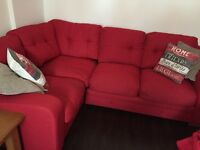 Red material corner sofa with fold out bed.