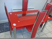 beautiful red glass dining table and 4 chairs. excellent condition. heavy and strong .