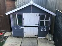 Wooden playhouse painted purple and pink