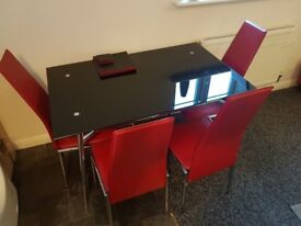 Black glass dinning table and 4 red chairs. Great condition. Collection only.