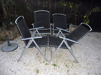 patio chairs 4 of with recling backs good condition black and silver and parosol base