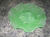 An attractive plae gree glass plate with a wavy edge.