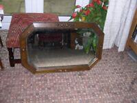 A vintage oak framed octagonal mirror with bevelled edges.