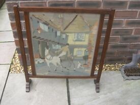 A wood framed fire screen with a glazed embroidery of a rider and horses.