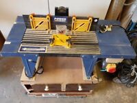 Router table with router and box of router bits