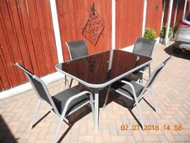 Table and 4 Chairs, will seat 6. Large Black Glass Like New. Bargain!!