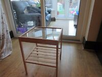 small table approx 15 inches square 16 inches high glass top slats below,