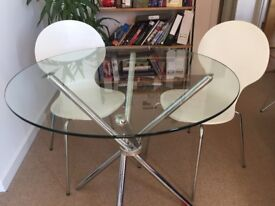Stylish circular glass-topped table with matching chairs!