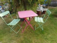 two green folding metal garden chairs and pink metal folding garden table