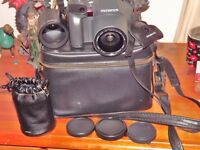 OLYMPUS is 10 S L R FILM CAMERA WITH CASE EXTRA LENS AND REMOTE AND CASE
