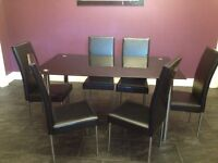 Black glass table with 6 high backed black chairs. Chrome legs. Table legs are remove able.
