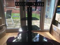 Black Glass Tv stand with Chanel to hide cables making a neat finish. Excellent condition.