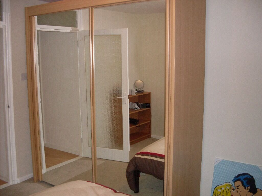 Large Wardrobe With Sliding Mirrored Doors And Shelf Storage
