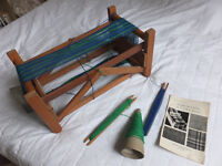 Two small hand operated weaving looms with various wool cones