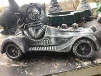 Stone garden ornament of a dog in racing car