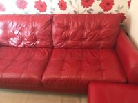 Red leather sofa with footstool with storage.